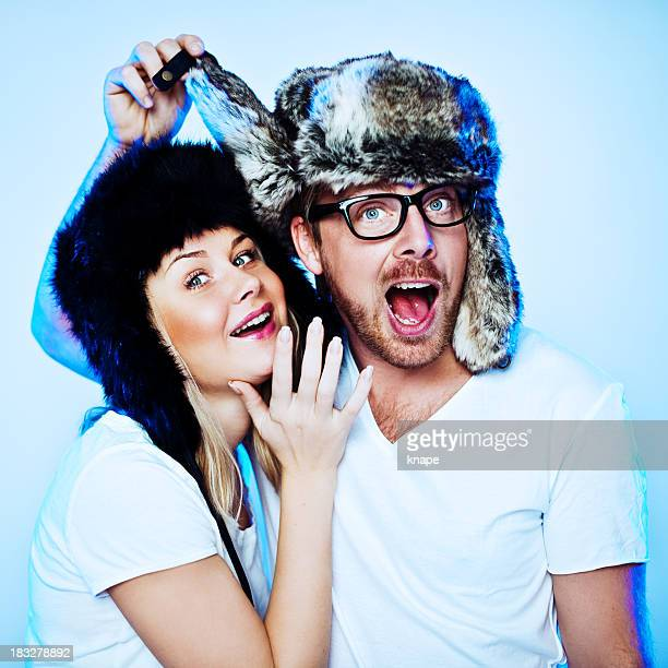 cute couple in fake fur hats - fur hat stock photos and pictures