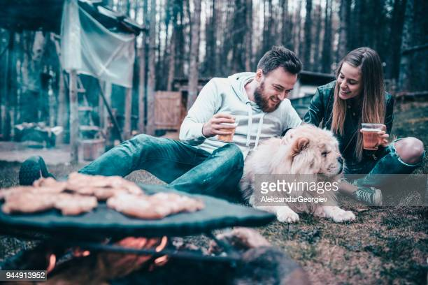 Cute Couple On Camping With Their Dog Making Barbeque