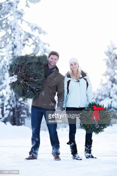 adorable young couple carrying wreath and christmas tree in snow - snow boot stock photos and pictures
