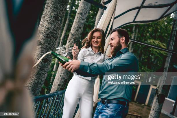 cute couple opening champagne bottle for their anniversary party - drunk wife at party stock pictures, royalty-free photos & images