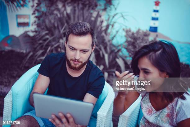 Cute Couple Playing Game on Digital Tablet in Backyard