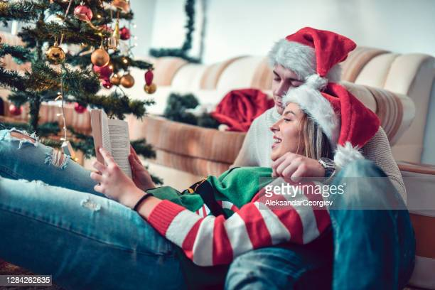 cute couple reading a book together on christmas eve - receiving stock pictures, royalty-free photos & images