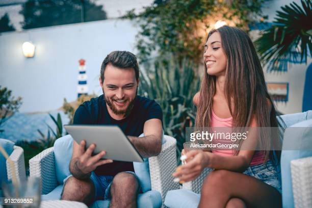 Cute Couple Video Conferencing on Digital Tablet in Backyard