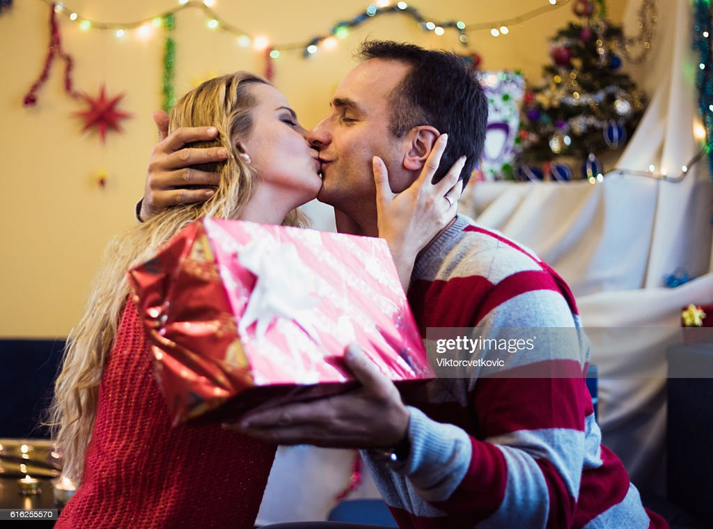 Cute couple with gift kissing of New Year eve. : Foto de stock