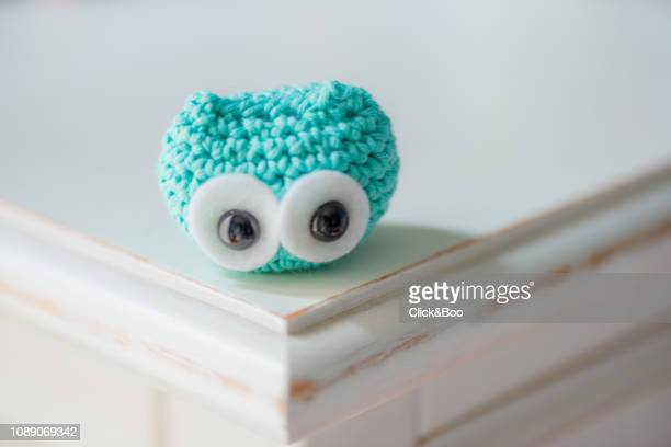 Cute crocheted little owl on a white surface (emerald colored)