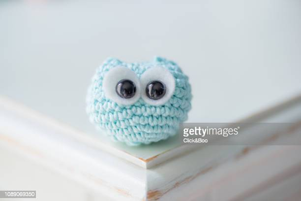 Cute crocheted little owl on a white surface (blue)