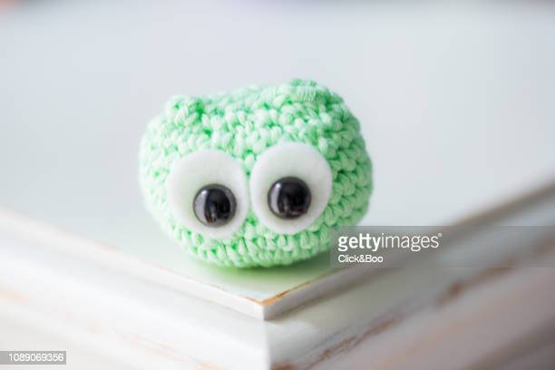 Cute crocheted little owl on a white surface (green)