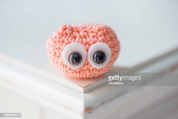 Cute crocheted little owl on a white surface (coral colored)