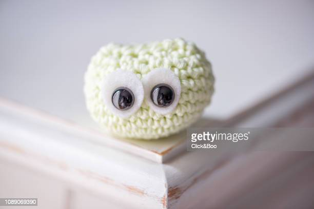 Cute crocheted little owl on a white surface (yellow)