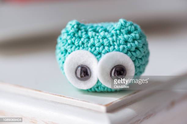 Cute crocheted little owl on a white surface (emerald green)