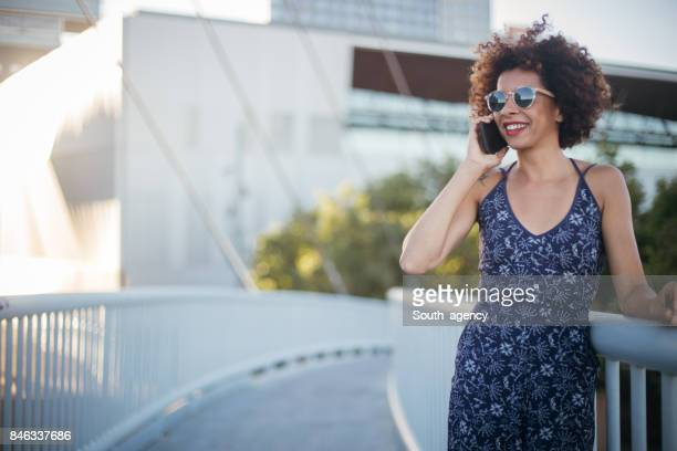 cute curly girl talking on the phone - blue dress stock pictures, royalty-free photos & images