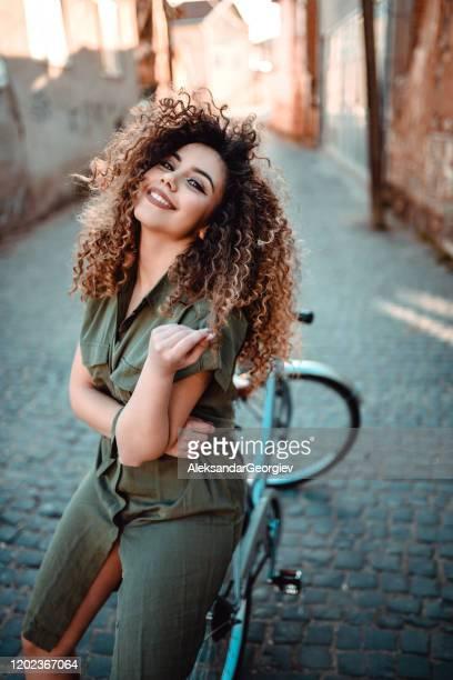 cute curly hair female sitting on bicycle - modella per artisti foto e immagini stock