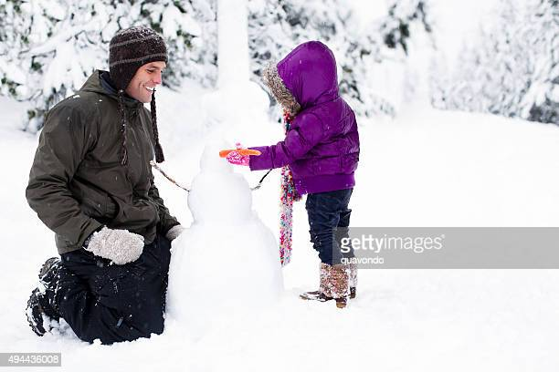 Cute Dad And Daughter Build Snowman