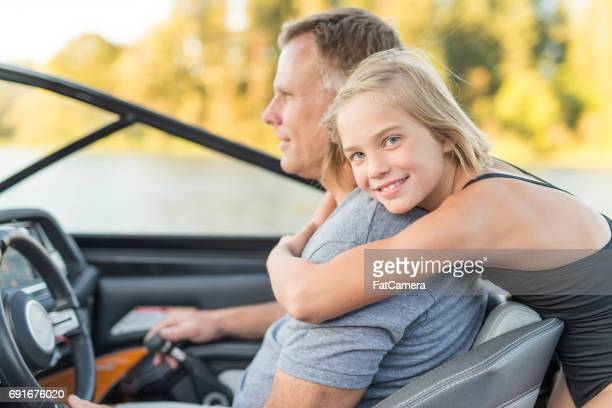 Cute daughter hugs her father on boat