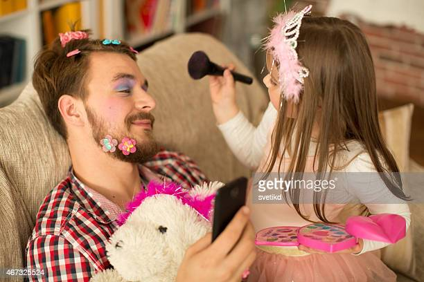 Cute daughter making up her father.