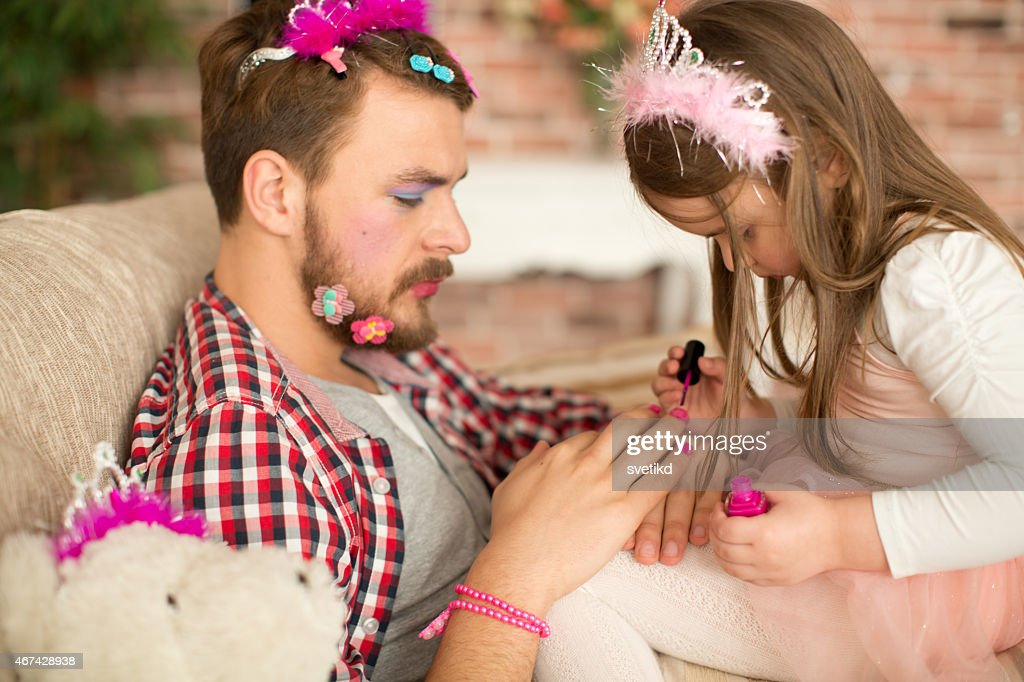 Cute daughter making up her father. : Stock Photo