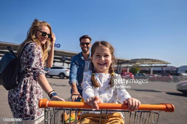 leuke dochter die in een winkelwagentje berijdt dat door haar ouders wordt geduwd - lagere schoolleeftijd stockfoto's en -beelden