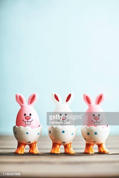 cute easter bunny trio in eggcups with blue background - easter photos stock pictures, royalty-free photos & images