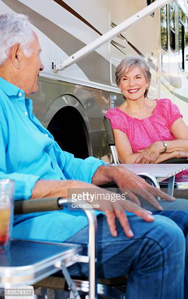 Cute elderly couple sitting by a caravan