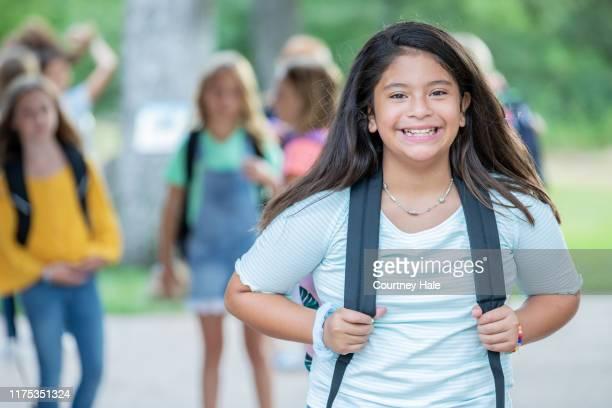 cute elementary age schoolgirl wearing backpack stands outside with group of friends - aluna da escola secundária imagens e fotografias de stock
