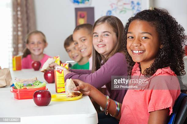 Cute elementary children having lunch at school