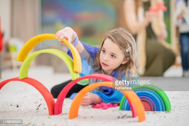 cute elementary girl building a rainbow structure - montessori education stock pictures, royalty-free photos & images