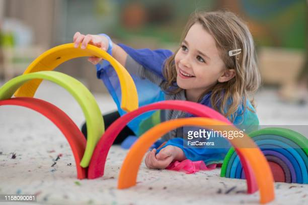 cute elementary girl building a rainbow structure - fatcamera stock pictures, royalty-free photos & images