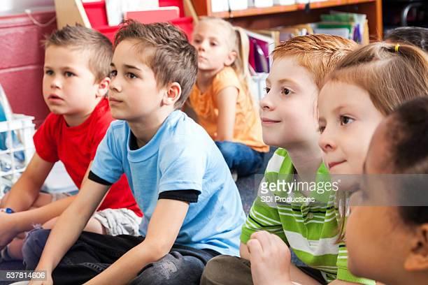 Niños lindo elemental escuchar durante historia de tiempo