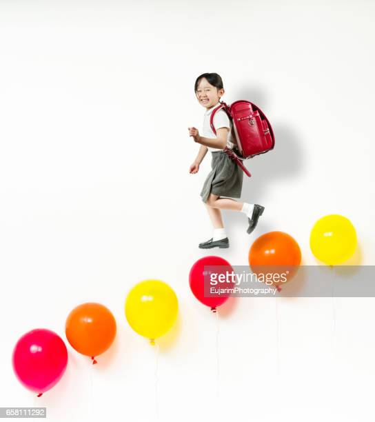 Cute elementary school girl going down balloon stairs