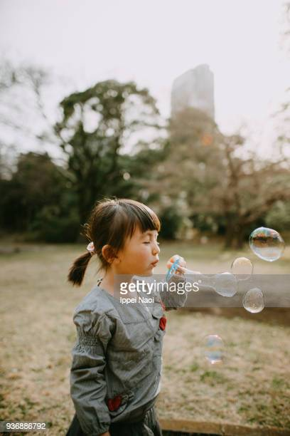 Cute Eurasian little girl blowing bubbles in park