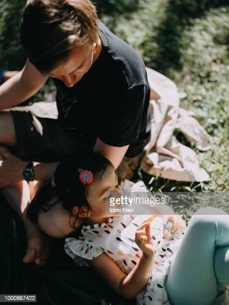 Cute Eurasian little girl relaxing on lap in park