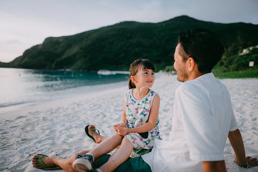 Cute Eurasian preschool girl sitting on father's lap on beach at sunset, Okinawa, Japan - gettyimageskorea