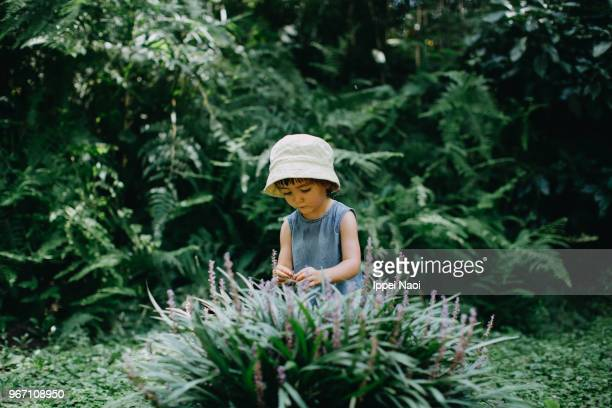Cute Eurasian toddler studying flowers