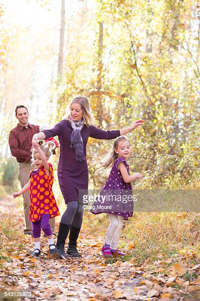 A cute family of five walk and dance during a fall time photo portrait session in Kalispell, Montana.