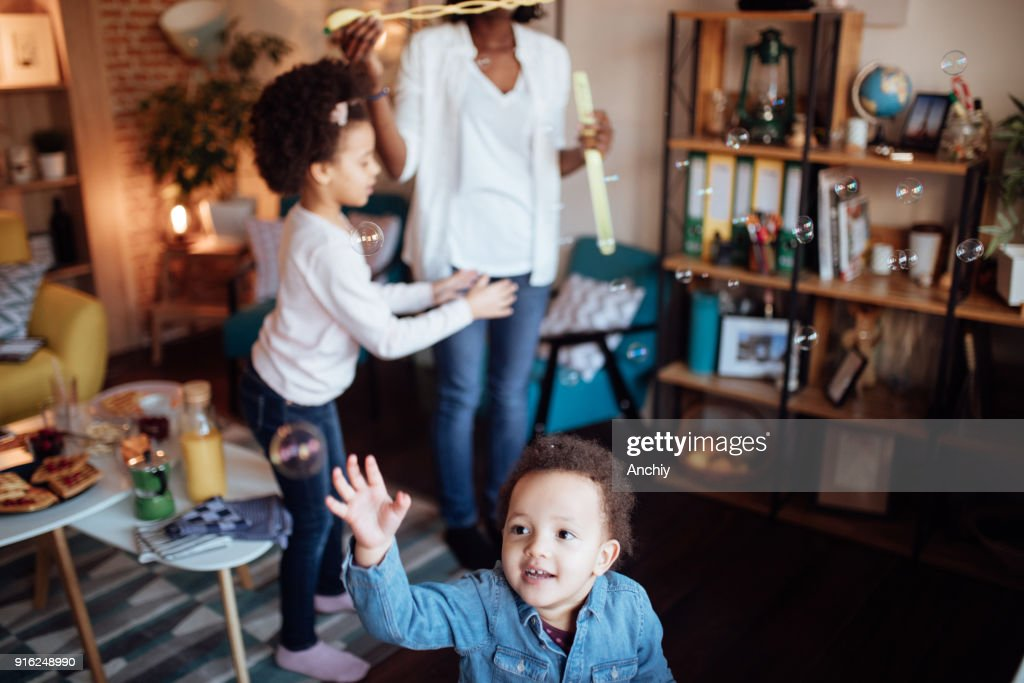 Cute family playing with soap bubbles : Stock Photo