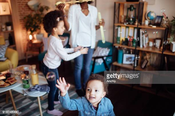 Cute family playing with soap bubbles