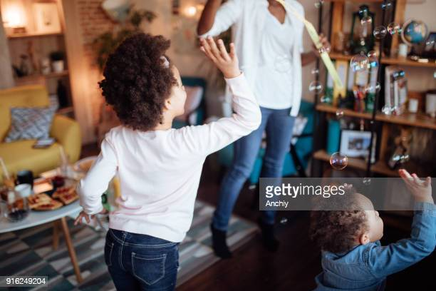 cute family playing with soap bubbles - interracial cartoon stock photos and pictures