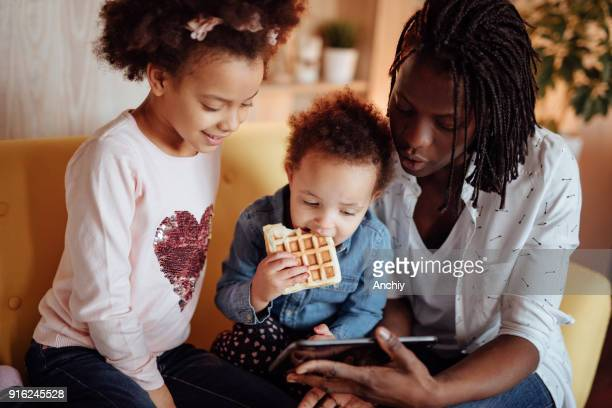 朝食をとりながらタブレットで漫画を見てかわいい家族 - interracial cartoon ストックフォトと画像