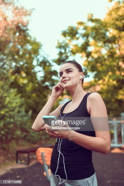 cute female and her smartphone playlist during outdoor training - colors soundtrack stock pictures, royalty-free photos & images