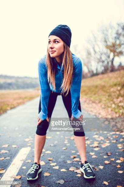 cute female athlete taking a break from running - hand on knee stock pictures, royalty-free photos & images