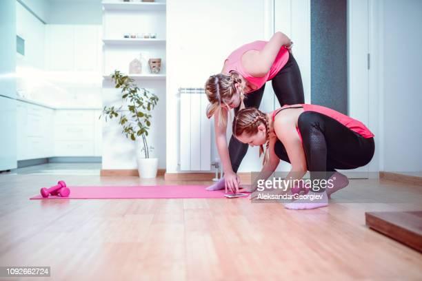 Cute Female Athletes Watching Yoga Tutorials