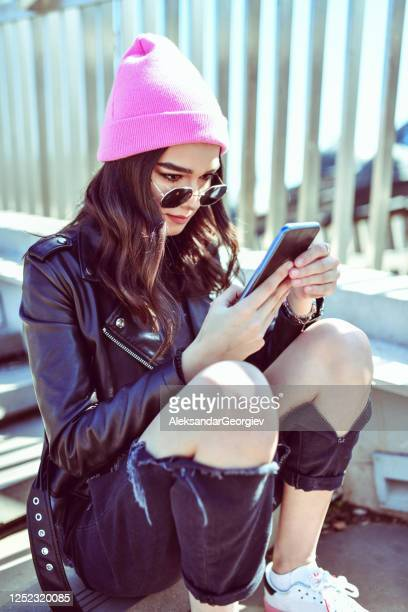 cute female browsing through social media on smartphone while sitting on stairs - punk music stock pictures, royalty-free photos & images