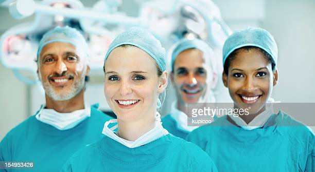 Cute female doctor smiling with team