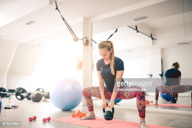 Cute Female Doing Squats with Kettle Bell Weight in Modern Gym
