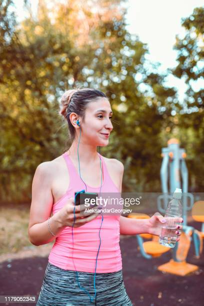 cute female drinking water and enjoying music while working out outside - colors soundtrack stock pictures, royalty-free photos & images