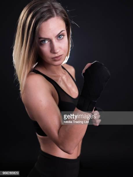 Modèle jolie femme fitness avec mains bandés posant et en regardant la caméra
