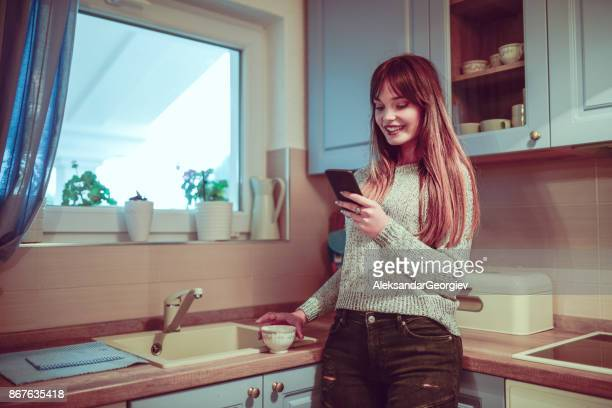 Cute Female in Kitchen Drinking Coffee and Blogging