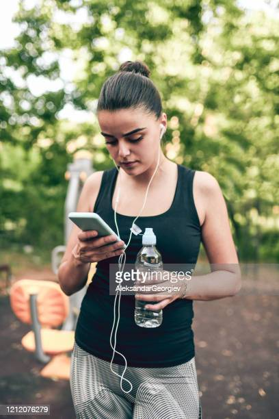 cute female looking at exercise results in park and refreshing with water - colors soundtrack stock pictures, royalty-free photos & images