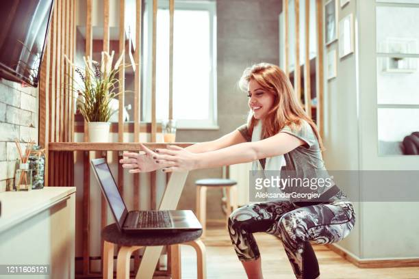 cute female practicing squats in kitchen - crouching stock pictures, royalty-free photos & images