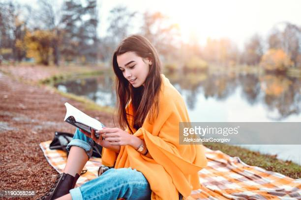 cute female reading a book in park - literature stock pictures, royalty-free photos & images